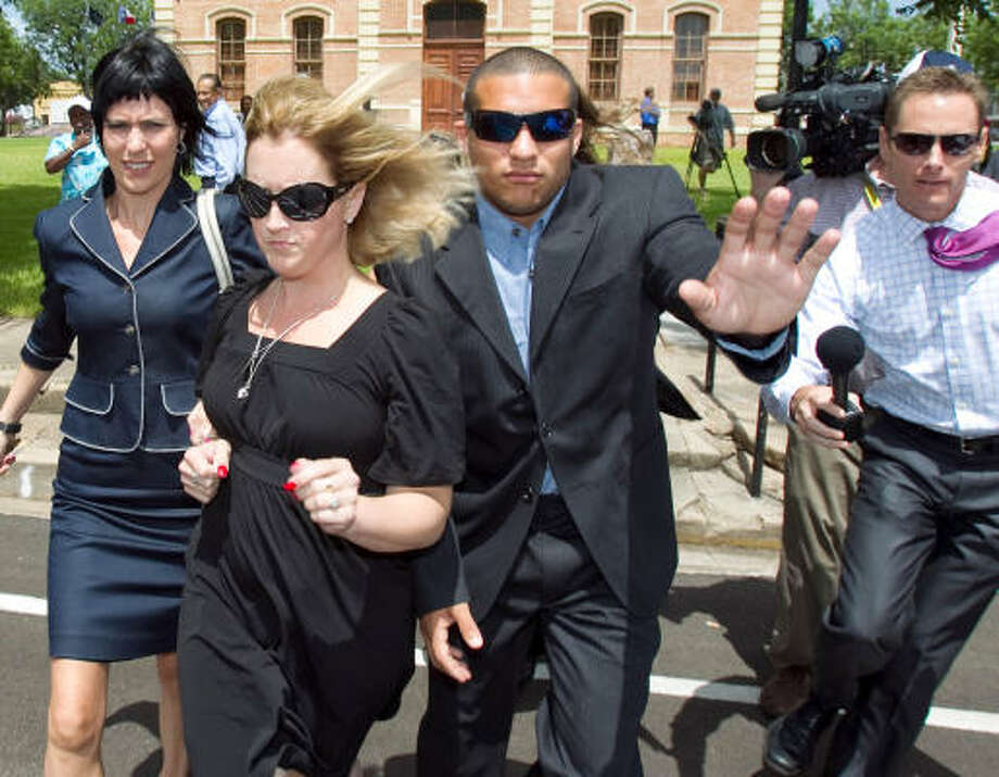 Nikki Araguz, center, leaves the Wharton County Courthouse on Friday after a judge temporarily barred her from spending or collecting her late husband's death benefits. Araguz's husband, Thomas Araguz III, was a firefighter who was killed in the line of duty. His family is contesting his wife's rights to the estate. Photo: Nick De La Torre, Chronicle