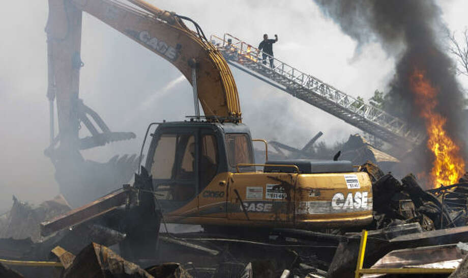 Firefighters take aim at a flare-up while heavy equipment moves in to clear rubble in the ruins of a north Houston warehouse that burned early Friday. Photo: Brett Coomer, Chronicle
