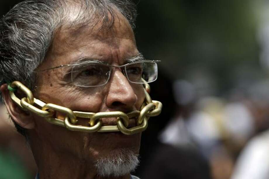 In this Aug. 7 photo, a man protests violence against journalists. On Wednesday, Jorge Luis Aguirre, a Mexican news reporter, announced the U.S. had granted him political asylum. Photo: Marco Ugarte, Associated Press