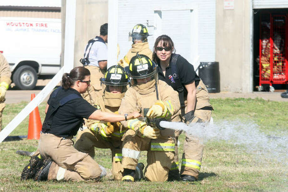 POINT AND SHOOT: Waltrip High School students Minesha Mathews and Amanda Macia learn how to control the water pressure with Houston firefighters Terri Salines and Irene Torres-Soto during the inaugural Camp Houston Fire. The Houston Fire Department Sirens organization, in association with Houston FD and Houston Independent School District, organized the camp to encourage young women to consider the fire service as a career option. Photo: Pin Lim, For The Chronicle