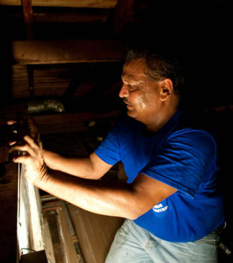 Masood Javed inspects a blower in a sweltering attic as he works on an air-conditioning unit. Javed is unable to drink water during the day because he's observing Ramadan Photo: Nick De La Torre, Chronicle