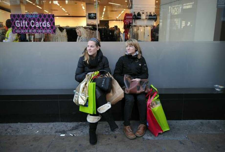 Two shoppers take a break outside a store on Oxford Street in central London. Photo: CARL COURT, AFP/Getty Images
