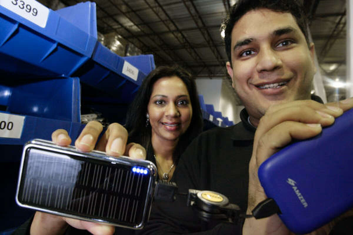 Pallavi Dinesh, left, of Fommy.com displays a battery charger. Her husband, Pinakin, shows a cover.