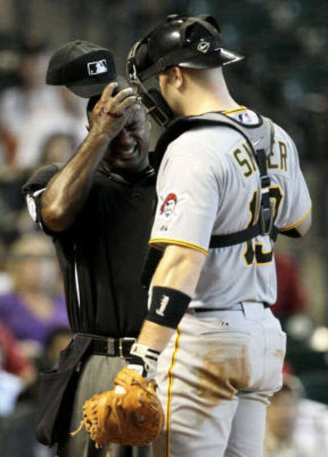 Home plate umpire Alan Porter holds his head after being hit by a Carlos Lee swing. Photo: Julio Cortez, Chronicle