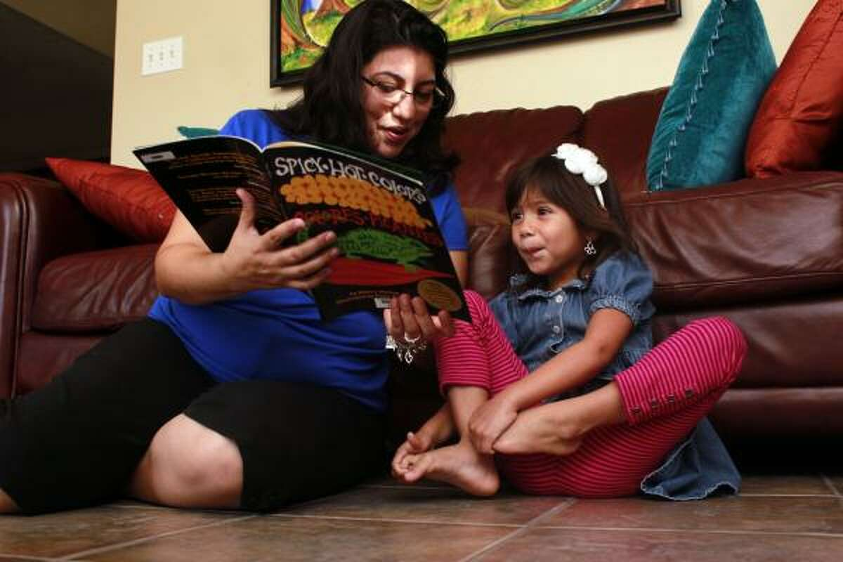 Lisa Salazar, 37, reads Sherry Shahan's Spicy Hot Colors: Colores Picantes to her daughter, Ava, 4, using The Family Literacy Involvement Program's reading kit.