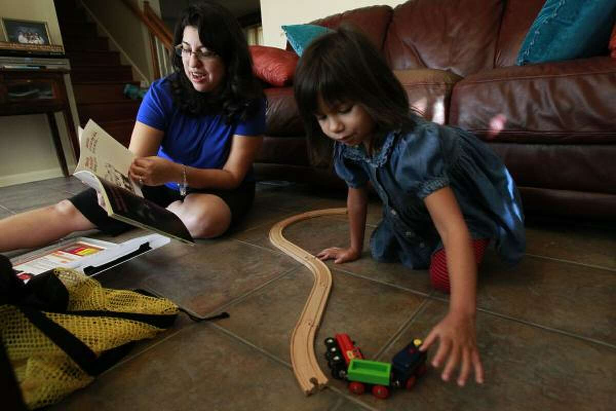 Ava Salazar plays with the toy train set provided by FLIP as her mom, Lisa Salazar, reads Donald Crews' book Freight Train to her.