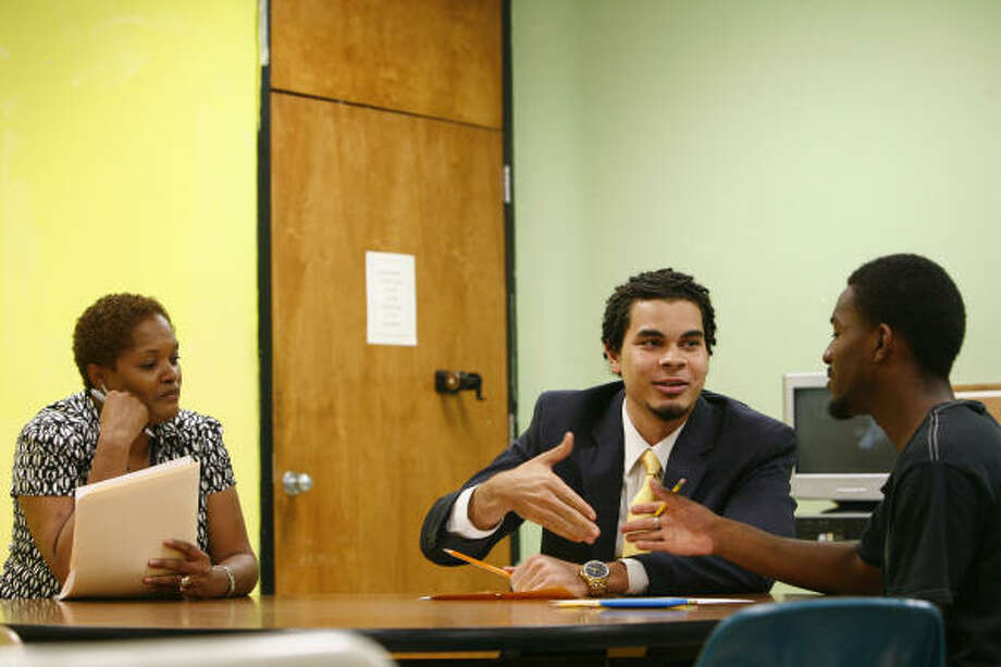 Prospect Mike Brown, center, shakes hands with Sharpstown High School senior Darnell Anderson as Paula McNeil evaluates candidates during a sample tutoring session Tuesday.? Photo: Michael Paulsen, Chronicle