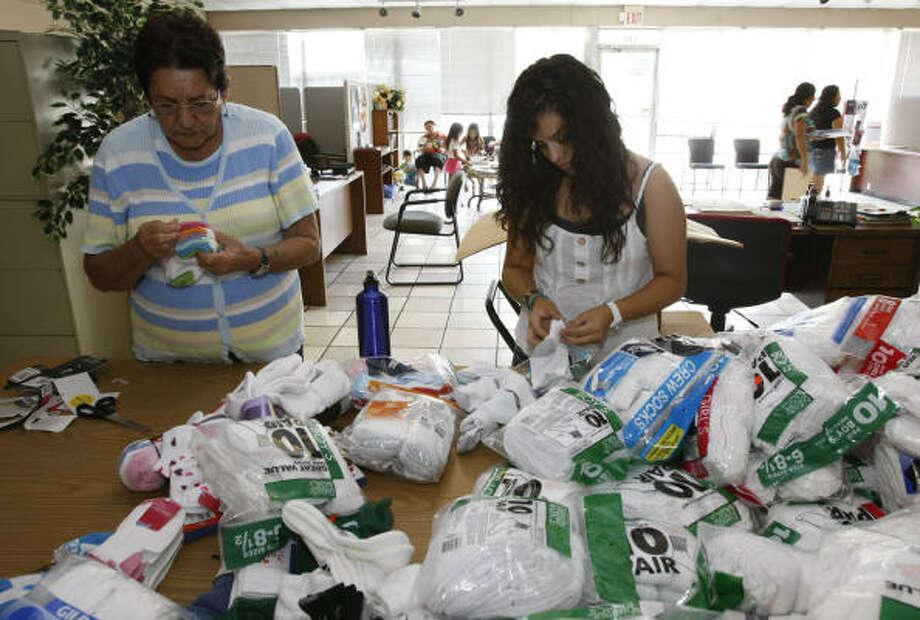 Elma Narváez, izq., y Anali Martínez, der., revisan calcetines y útiles escolares que La Rosa entregará a familias de bajos ingresos. Photo: Julio Cortez, La Voz