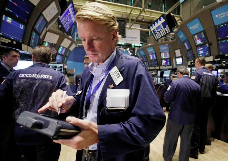 In this Aug. 1, 2011, trader John Bowers works on the floor of the New York Stock Exchange. Global stock markets tumbled Tuesday, Aug. 2, after downbeat U.S. data fueled fears the world's largest economy might be sliding back into recession.(AP Photo/Richard Drew) Photo: Richard Drew, STF / AP