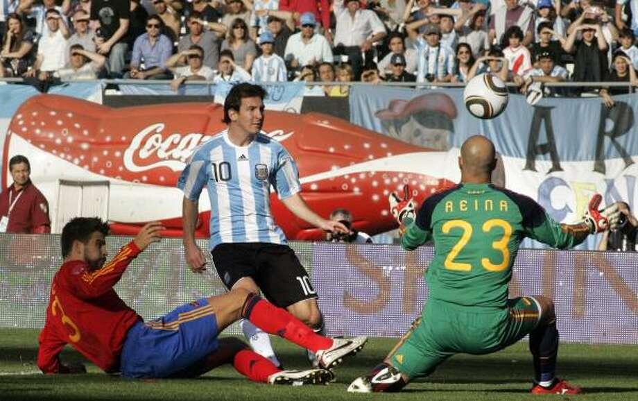 Argentina's Lionel Messi, center, scores over Spain goalkeeper Pepe Reina. Photo: Alberto Raggio, AP
