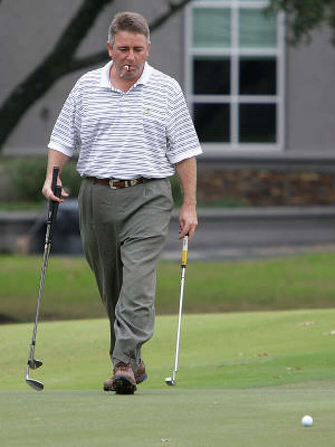 Craig Phillips smokes a cigar as he carries three clubs on the 7th hole on the Cypress Creek course. Photo: Karen Warren, Chronicle