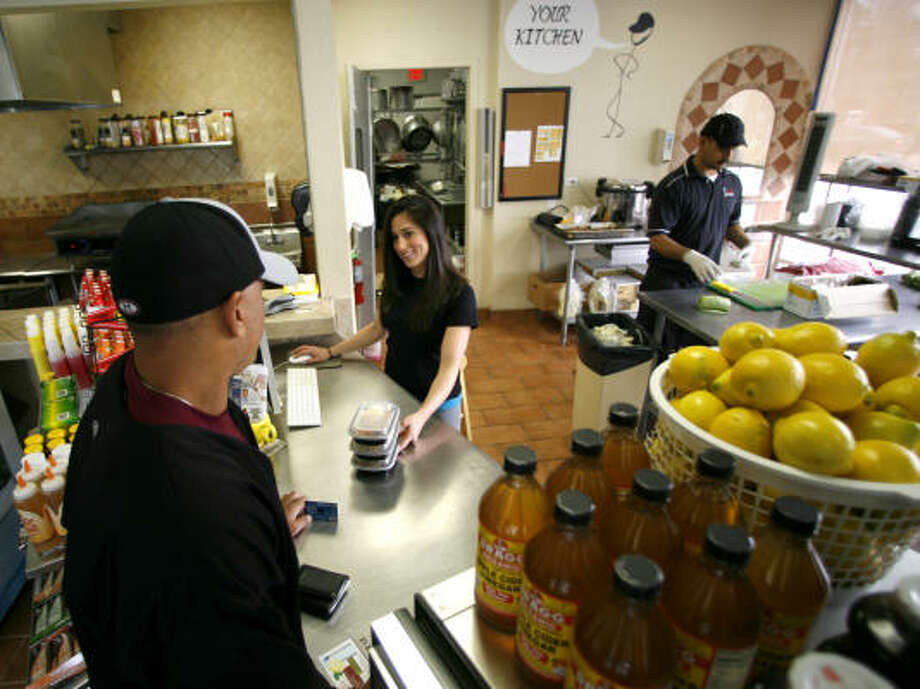 Tracie Kochak, manager of the My Fit Foods at Kirkwood and Memorial, helps customer Tony Metoyer. My Fit Foods is the largest local chain. Photo: Karen Warren :, Chronicle