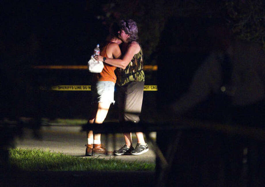 Women embrace at the northeast Harris County home where Jayden Woodward was found dead inside a vehicle Tuesday night. Photo: Brett Coomer, Chronicle