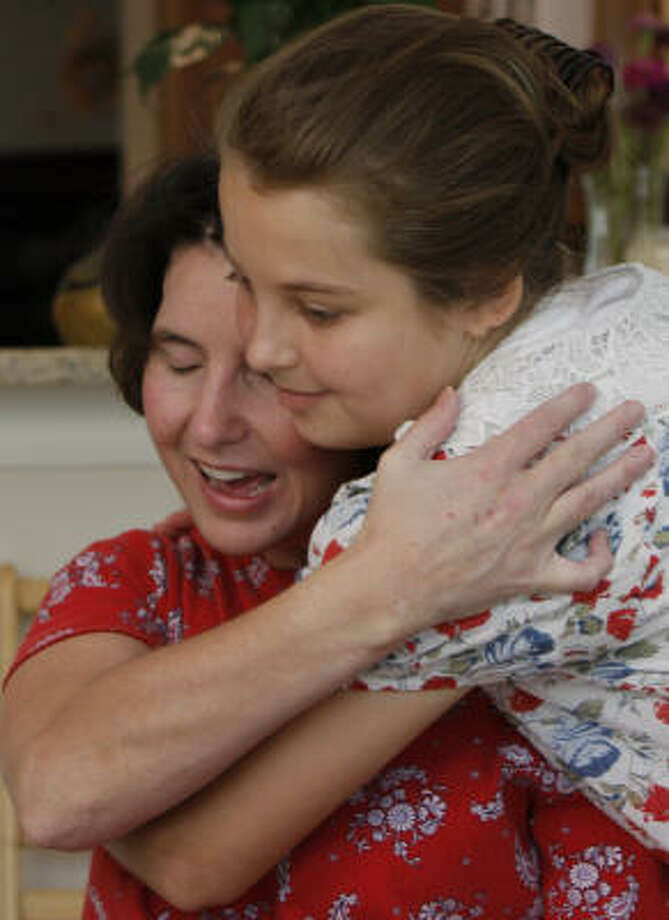 Dianne Helms' left arm doesn't respond, so she has to embrace daughter her daughter, Leanne, all the harder with her right. Helms is working to walk and speak in her own voice again. She uses a keyboard to communicate. Photo: Yasmeen Smalley, Chronicle