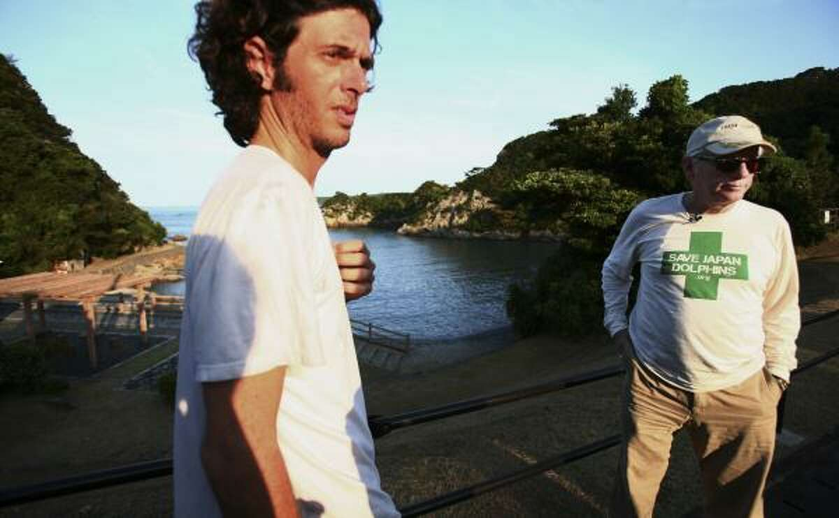 """Marine mammal specialist Ric O'Barry, right, and his son Lincoln stand near the cove where dolphin killings took place in Taiji, western Japan, the subject of the Oscar-winning documentary """"The Cove."""""""