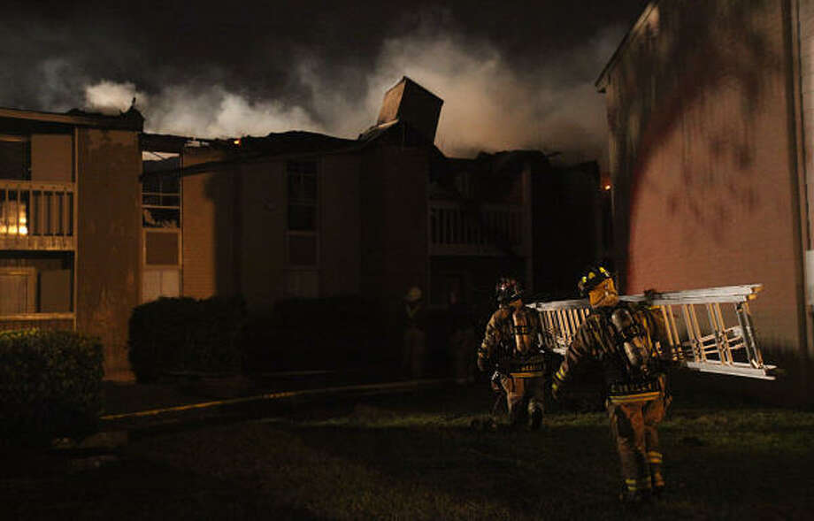 Pasadena firefighters bring in a ladder as they work to extinguish a fire at the Cinnamon Ridge apartments in Pasadena on Monday.  A fast-moving blaze gutted a building in the complex. Photo: Mayra Beltran, Houston Chronicle