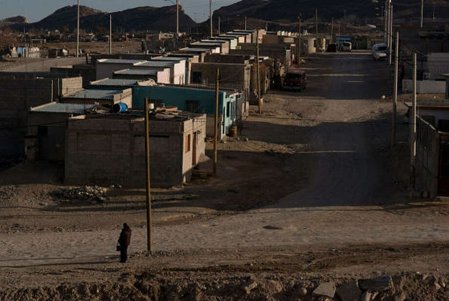 From the mountainside neighborhood where Irma Monreal lives, she has a view of Juarez sprawling below her and can see the lights and paved streets of El Paso across the Rio Grande. Photo: Julian Cardona, Chronicle