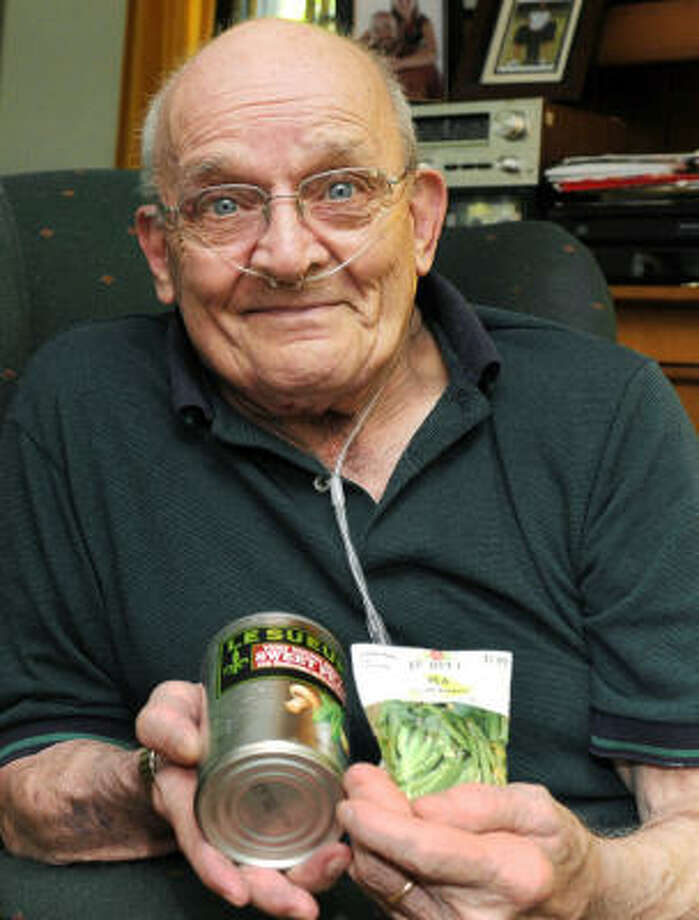 Ron Sveden, shown in July at his home in Brewster, Mass., holds a can of peas and bag of pea seeds — gifts he received from friends. Photo: Merrily Lunsford, Associated Press