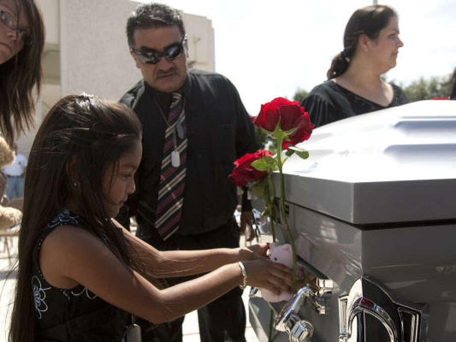 Kassandra Infante, left, places a stuffed animal on the casket of her her father, Jesse Infante, at Houston National Cemetery on Friday. Photo: Brett Coomer, Chronicle