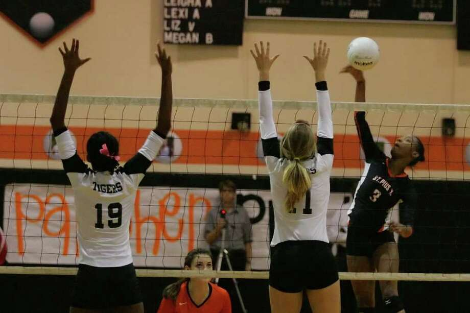 Brianna Reid of St. Pius takes her shot as Sakile Simmons and Emily Sweet try to make the block at the September 28th game.   Photo by Matthew White Photo: Matthew White, Freelance / Freelance