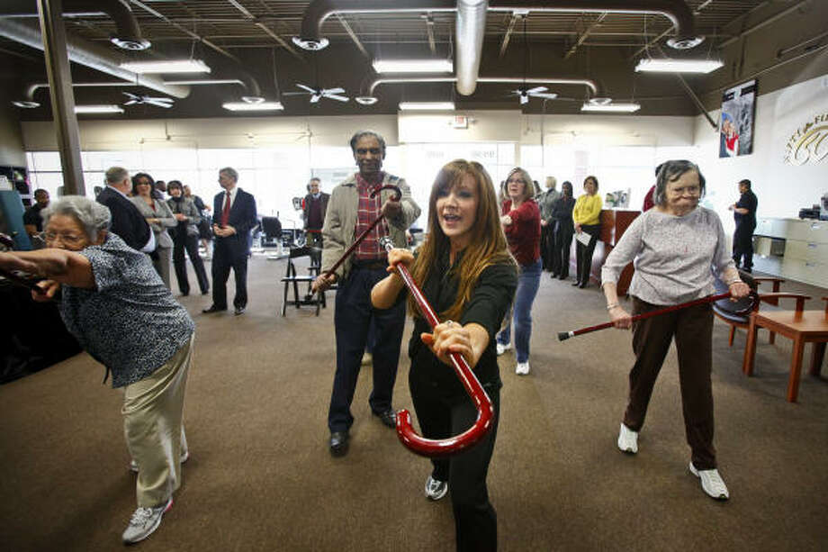 WOR-OUT CANE: Fitness coach, Jill Best, center, leads a group of senior citizens, Obdulia Guerra, left, Arthur Mangaroo and Ann Badders through a variety of Cane-Fu exercises during the grand opening celebration of Nifty after Fifty center in the Memorial City area on Jan. 12.  Cane Fu is new exercise trend for seniors that uses a combination of aerobic training and self-defense while helping improve balance and coordination. Photo: Michael Paulsen, Chronicle