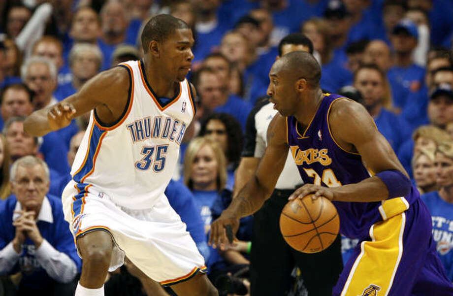 Lakers guard Kobe Bryant drives to the basket against Thunder forward Kevin Durant. Photo: Alonzo Adams, AP