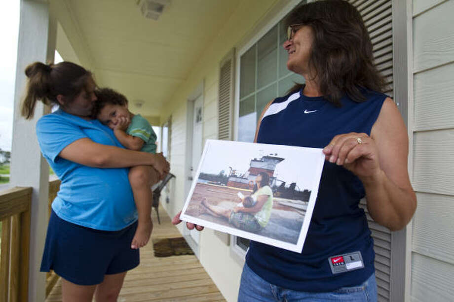 Margaret Shiver holds a photo taken two years ago while she and her husband were spending their nights on a tugboat. At left are daughter Brianna and grandson Dewayn. Photo: Karen Warren, Chronicle