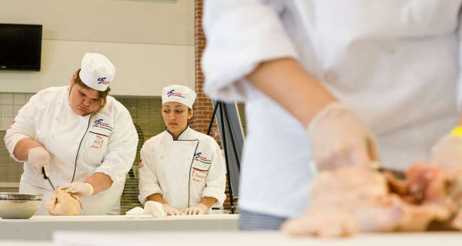 Teammates Ashley Rothrock, left, and Emily Murphy aim for precision and perfection during the poultry portion of the National Restaurant Association Educational Foundation's ProStart Invitational on Saturday at Westside High School. Photo: Nick De La Torre, Chronicle