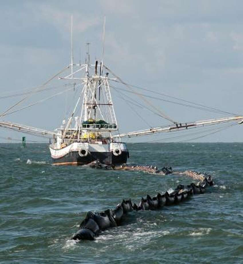 A shrimp boat pulls an oil retention boom through near Dauphin Island, Ala., on Sunday. Choppy seas have idled some vessels used to keep oil from hitting vulnerable beaches and marshes. Photo: Dave Martin, AP