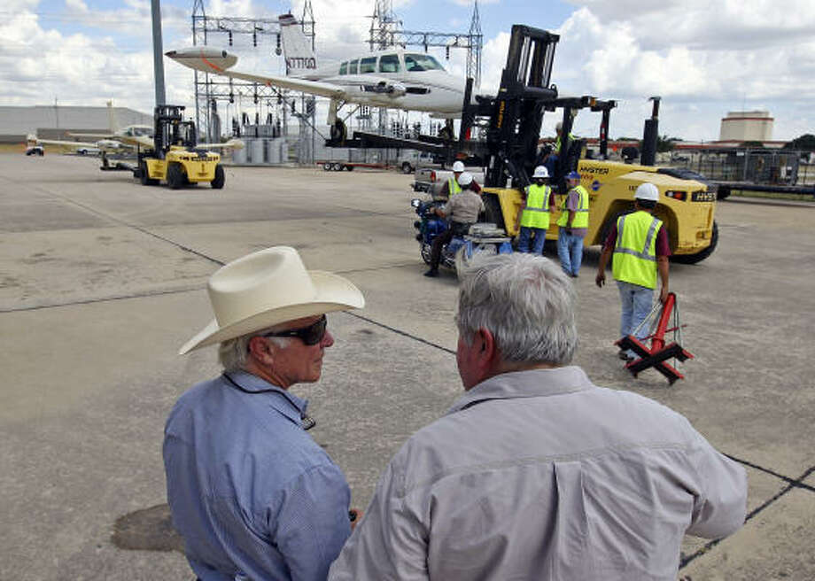 Larry Mahan, left, and George Harris watch as their planes are moved to a new home where the aircraft will become teaching tools for St. Philip's College in San Antonio. Photo: EDWARD A. ORNELAS, San Antonio Express-News