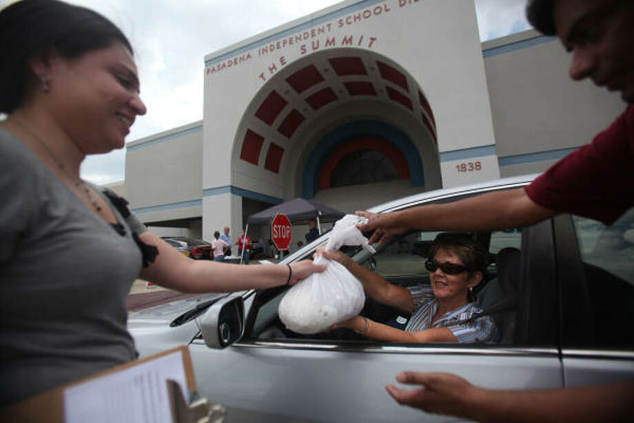 Debbie Styron, 57, of Deer Park, gives of a bag of prescription drugs on Saturday to Stephanie Eguia and Sanjay Gupta at a drug take-back site in Pasadena. Photo: Mayra Beltran, Chronicle