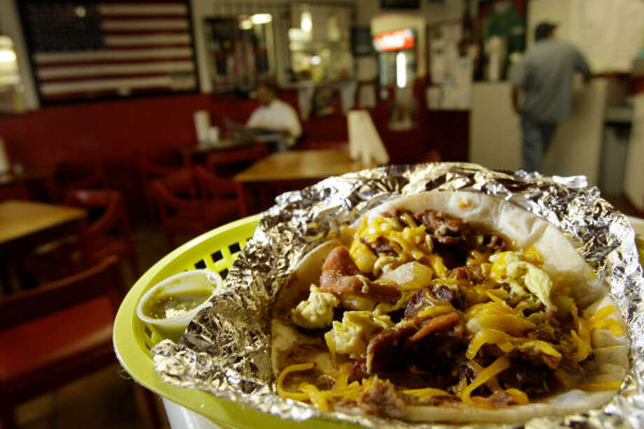 Villa Arcos customers with to-go orders may find it hard to resist eating their tacos before they get home. Photo: Melissa Phillip :, Chronicle