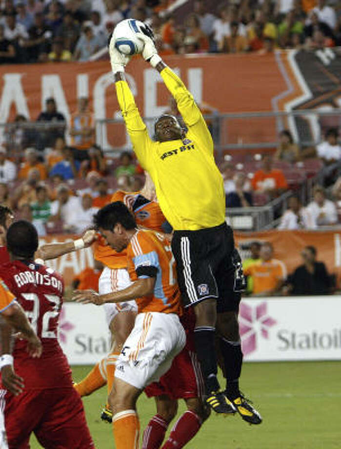 Fire goalkeeper Sean Johnson goes up over Brian Ching for a save in the first half. Johnson lost control of the ball when he came down, and Ching put the ball in the back of the net for a goal. Photo: Bob Levey, Getty Images
