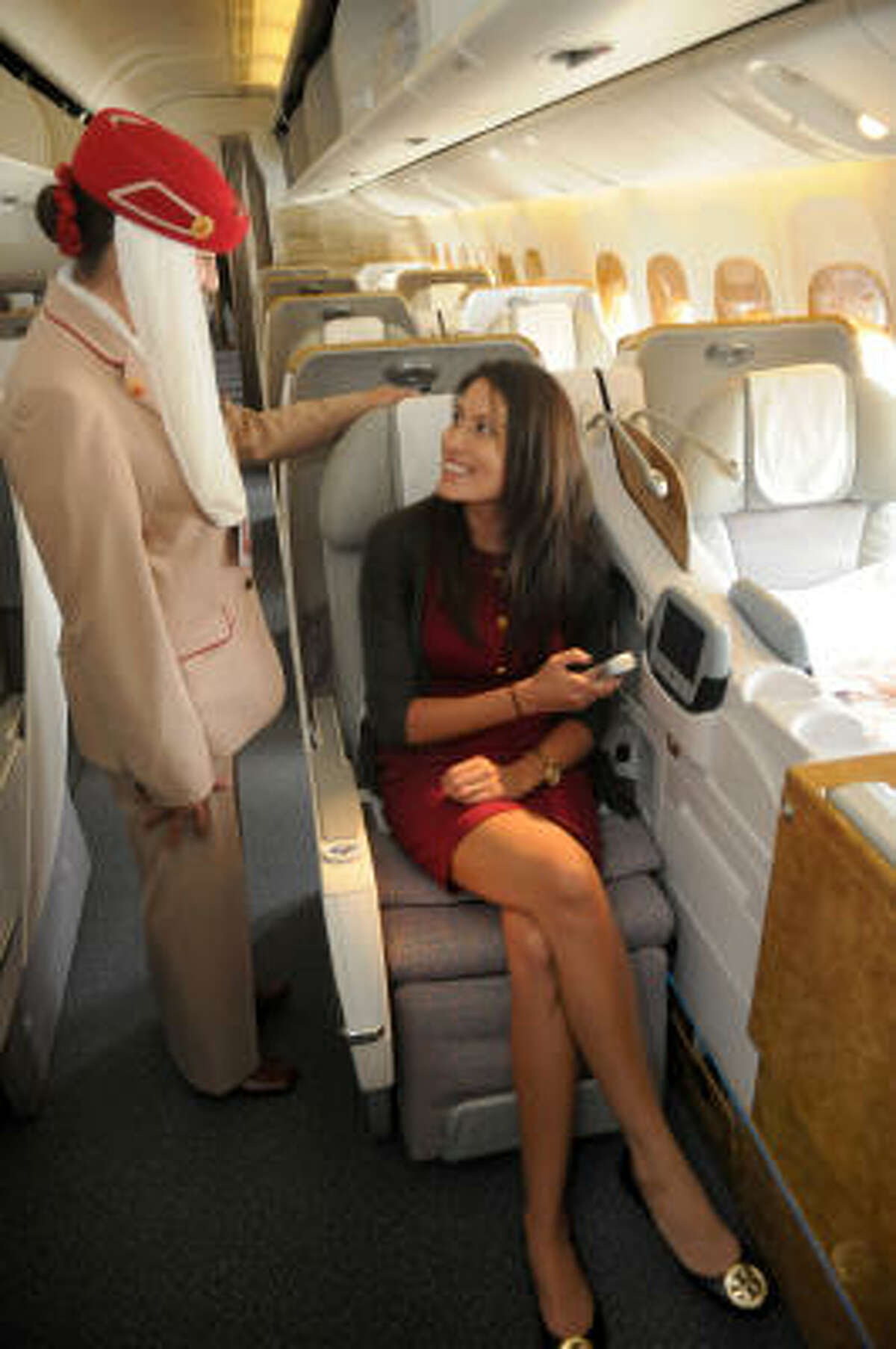 Laureen Lucas, right, project manager of public relations for FKM in Houston, with senior airport service agent Sara O'Leary of Humble, checks out a business-class seat on an Emirates Boeing 777 during a media tour the carrier offered this week.