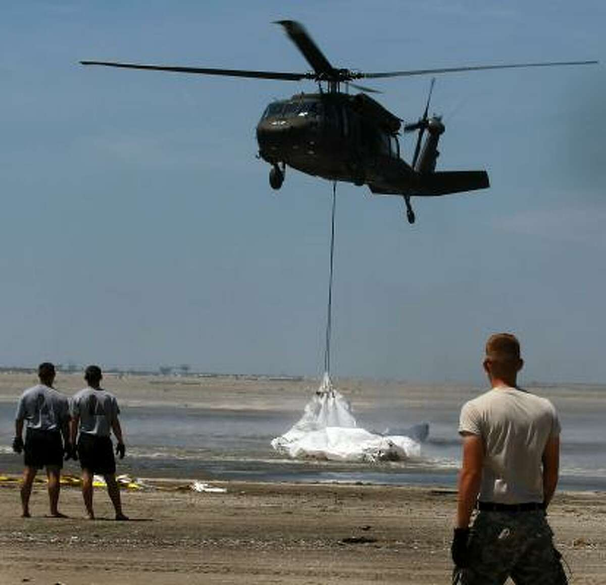 A Louisiana National Guard helicopter airlifts sling load sand bags into place as they create a barrier in an attempt to protect an estuary from the massive oil spill on May 10, 2010 in Lafourche Parish, La.