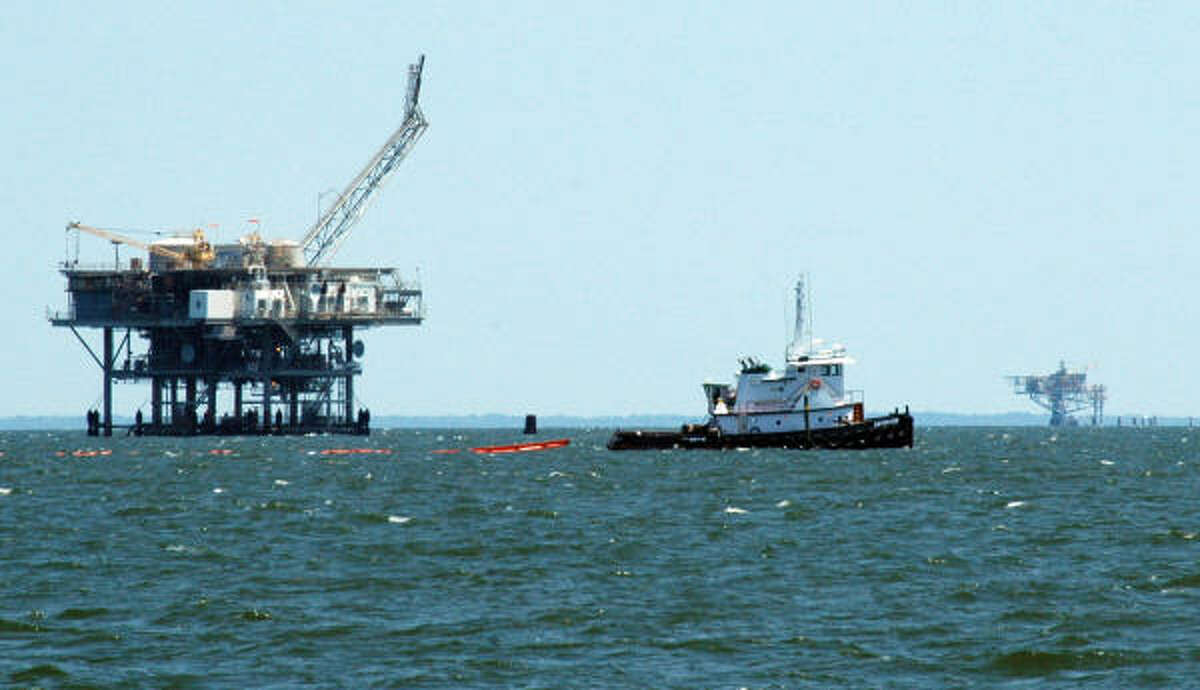 A tugboat pulls orange booms in Mobile Bay near Mobile, Ala., Monday, May 10, 2010. The state plans to seal off the bay from the oil spill using gates made of the oil-blocking barriers. Natural gas platforms are visible in the background.