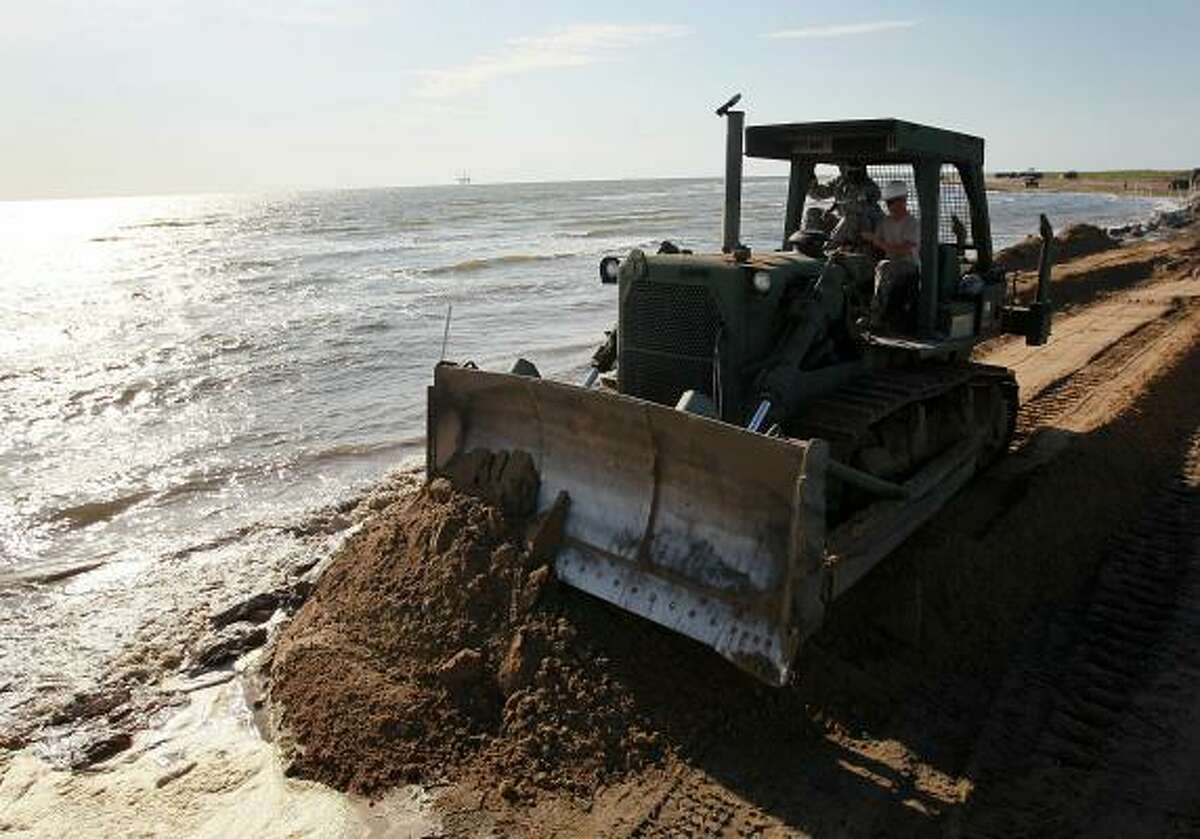 Louisiana National Guard use a bulldozer to create a earthen barrier as they try to protect an estuary from the massive oil spill on May 10, 2010 in Lafourche Parish, La.