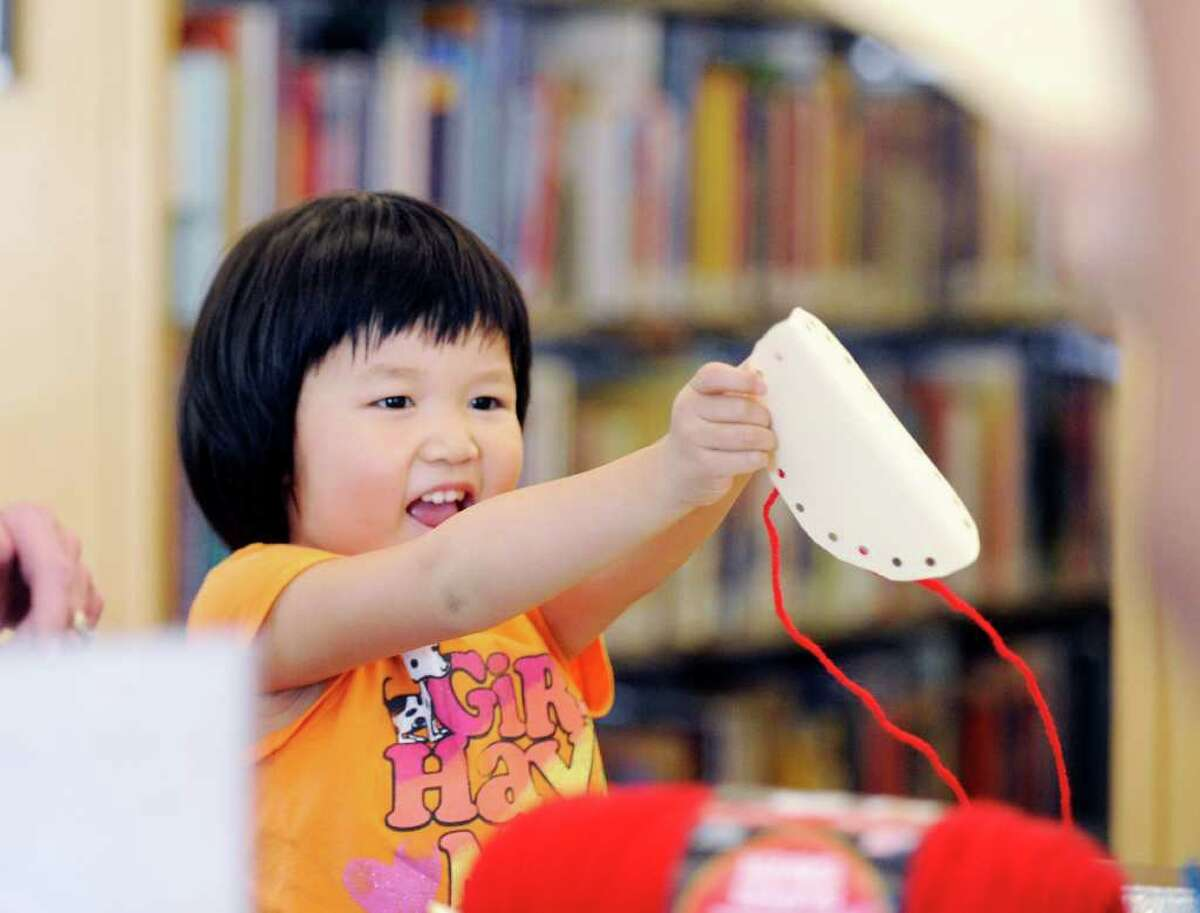 """Lydia Wang, 5, of Greenwich, smiles while making a fortune cookie from construction paper during the drop-in craft afternoon for children that is a part of the """"One World, Many Stories"""" summer reading program at Greenwich Library, Tuesday afternoon, Aug. 2, 2011."""
