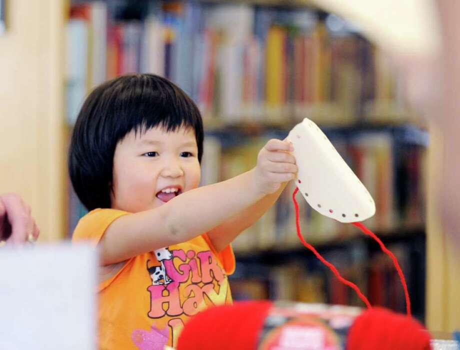 "Lydia Wang, 5, of Greenwich, smiles while making a fortune cookie from construction paper during the drop-in craft afternoon for children that is a part of the ""One World, Many Stories"" summer reading program at Greenwich Library, Tuesday afternoon, Aug. 2, 2011. Photo: Bob Luckey / Greenwich Time"