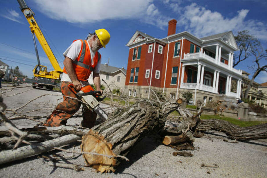 Kenneth Adison, 50, cuts up dead wood for removal as part of the city of Galveston's efforts to clean up remaining Ike debris. Today is the city's deadline to get debris to the curb. Photo: Mayra Beltran, Chronicle