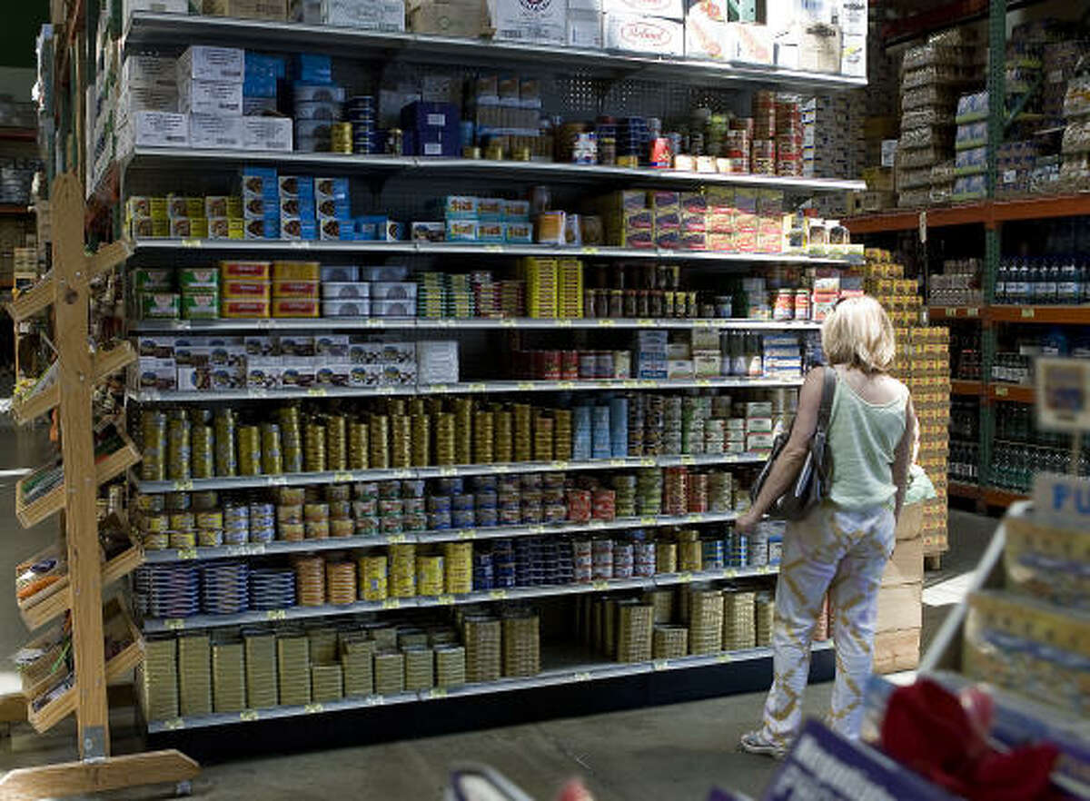 A customer looks over the canned seafood selection at the Phoenicia Specialty Foods store in west Houston.