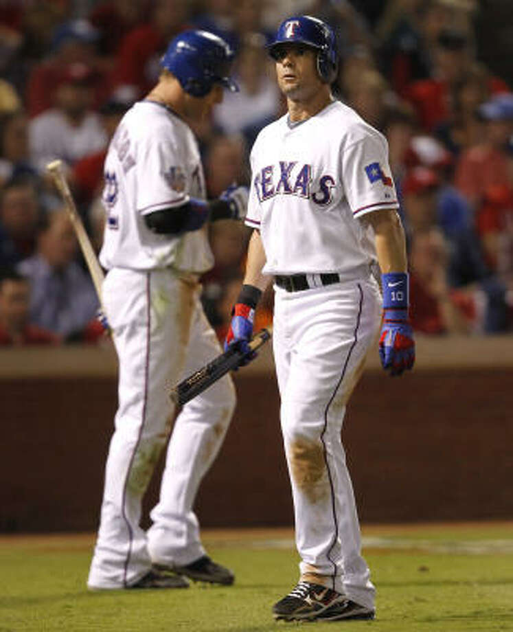 The Rangers' Michael Young, right, walks away after striking out in the seventh inning. Photo: Ron Jenkins, MCT