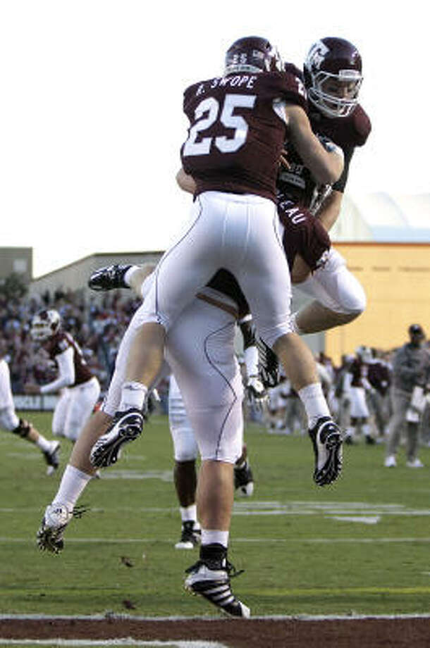 A&M wide receiver Ryan Swope (25) and quarterback Ryan Tannehill, right, jump on tight end Hutson Prioleau, center, after he caught a 1-yard touchdown pass from Tannehill in the first quarter on Saturday. Photo: Julio Cortez, Chronicle