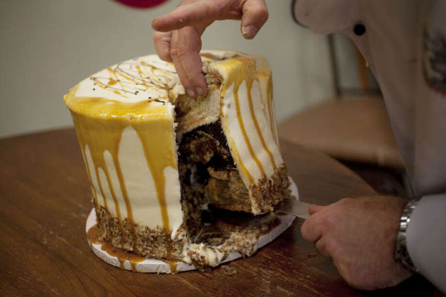 Three Brothers Bakery owner Robert Jucker cuts the first slice of pumpecapple, a cake with a pumpkin, apple and pecan pie inside. Photo: Mayra Beltran, Houston Chronicle