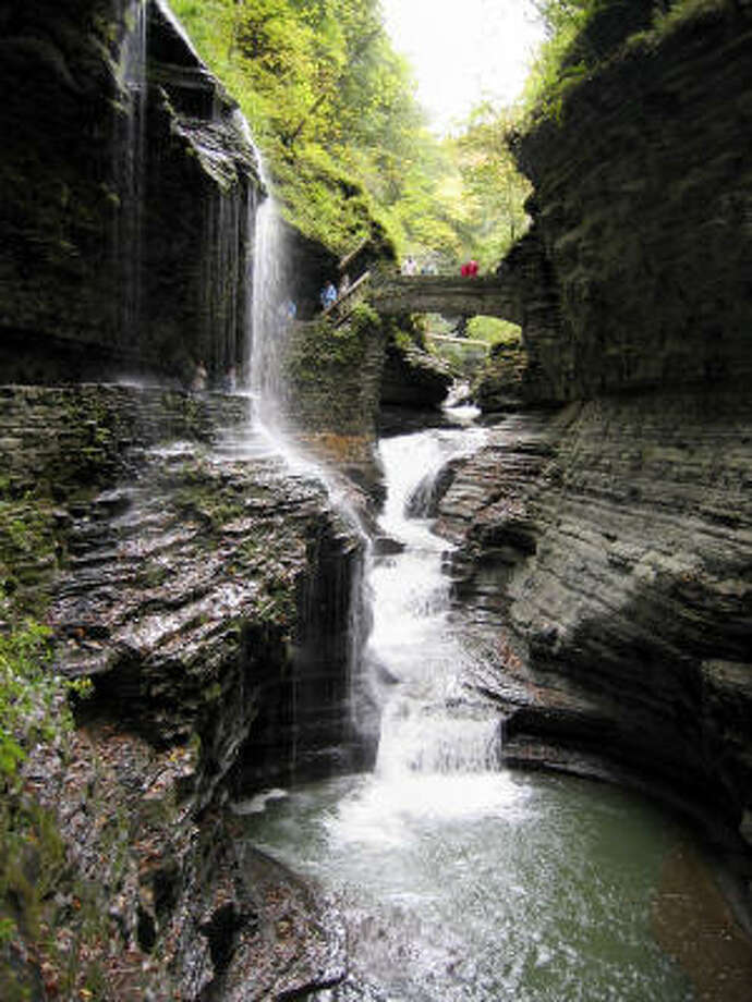 Visitors are dwarfed by a waterfall as they make their way along a trail through a spectacular gorge in Watkins Glen State Park, at the southern tip of Seneca Lake, part of the Finger Lakes region of west-central New York. Photo: Ann Levin, Associated Press