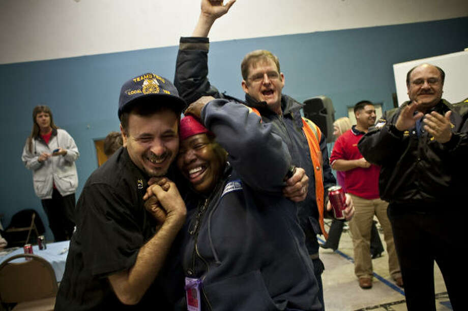 Lazaro Pastor, left, and Gwendolyn Henry, both customer service agents at Continental Airlines, cheer when they hear the vote count Friday at the local Teamsters union hall. Photo: Eric Kayne:, For The Chronicle