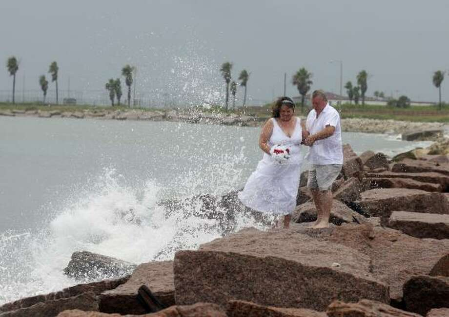 Grace Eaton, 50, and Dan Eaton, 62, from Leander, Texas, get splashed while having photos taken after renewing their vows for their 30th wedding anniversary on South Parde Island, Tx. as Tropical Storm Alex grows in the Gulf of Mexico and will likely form into a hurricane Tuesday. Photo: EDWARD A. ORNELAS, SAN ANTONIO EXPRESS-NEWS
