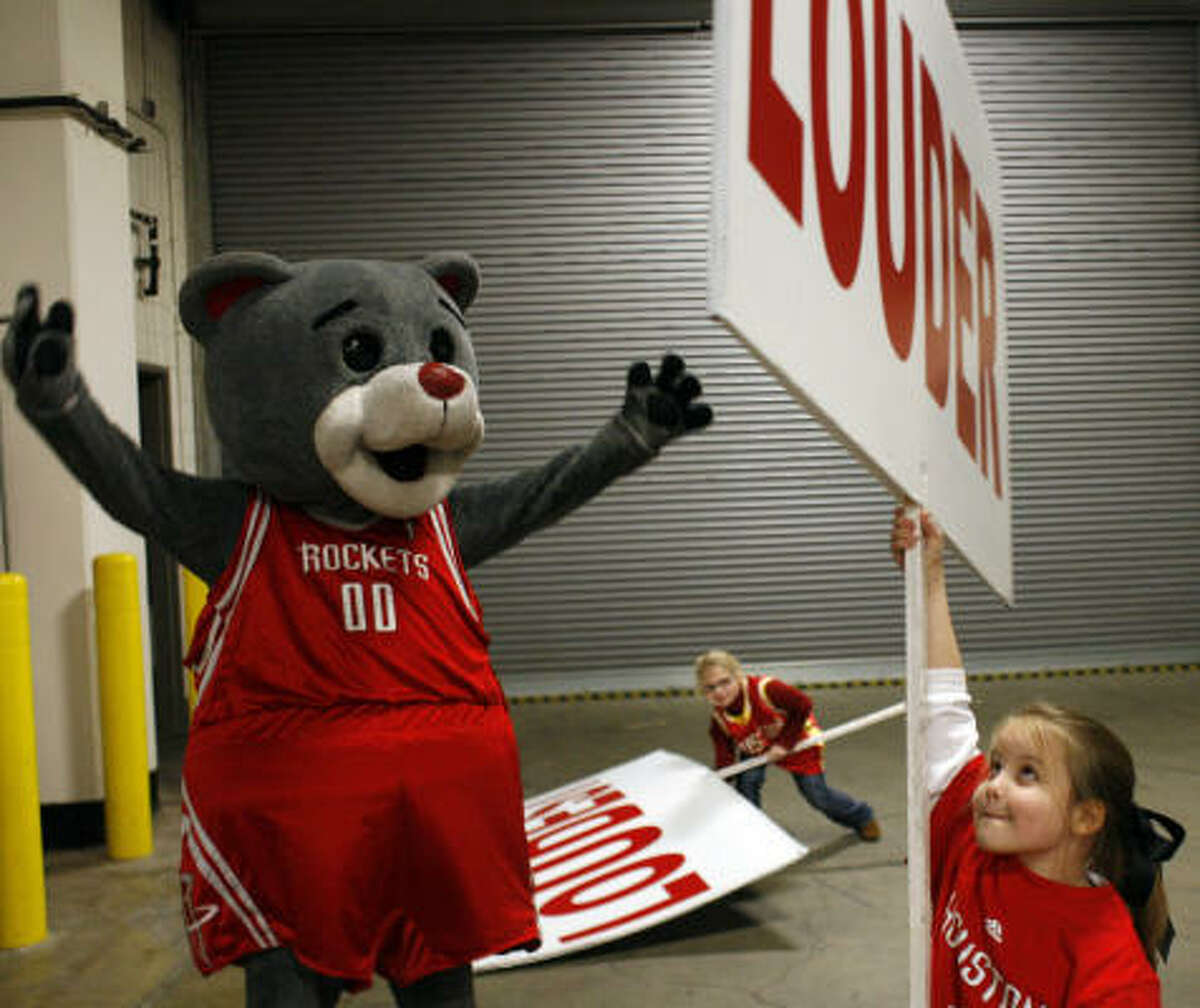 Clutch, aka Robert Boudwin, the Rockets mascot, gives helpers Carol Ann Caswell, 8, right, and Rachael Marglous, 9, tips before a recent game at the Toyota Center.