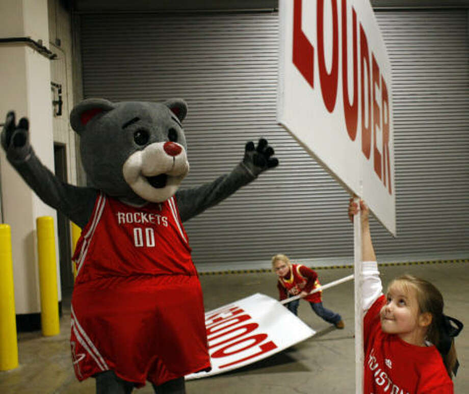 Clutch, aka Robert Boudwin, the Rockets mascot, gives helpers Carol Ann Caswell, 8, right, and Rachael Marglous, 9, tips before a recent game at the Toyota Center. Photo: Johnny Hanson, Chronicle