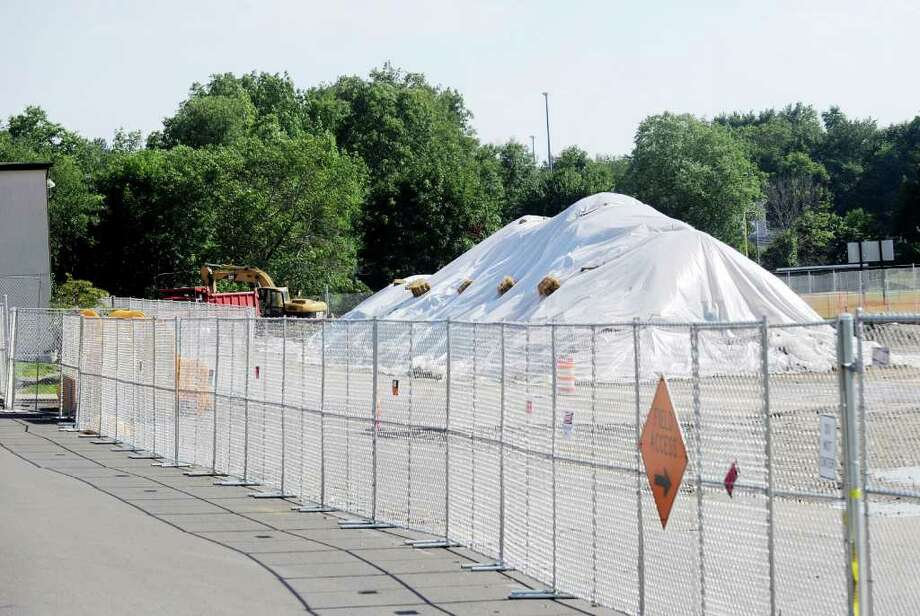 A tarp covers dirt mounds at Greenwich High School, Tuesday afternoon, Aug. 2, 2011. Greenwich High School playing fields are closed until further notice after testing discovered toxins in the soil unearthed during the auditorium project. Photo: Bob Luckey / Greenwich Time